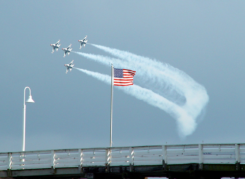 Free Picture: Photo of four F-16 Fighting Falcons flying in formation just behind an American flag at an airshow.