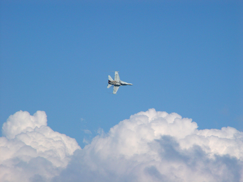 Free Picture: Photo of the bottom view of an F/A-18 Hornet fighter jet in among the clouds as it makes a turn.