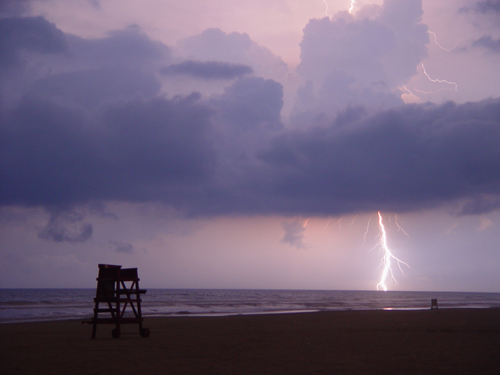 Free Picture: Photo of a bolt of lightning striking over the ocean near a lifeguard tower in Daytona Beach, FL.