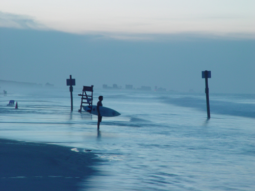 Free Picture: Photo of a lone surfer in Ponce Inlet, Florida looking out at the ocean with surfboard ready in hand.