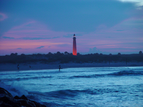 Free Picture: Photo of the Ponce Inlet Lighthouse at dusk as waves are crashing off the jetty rocks.