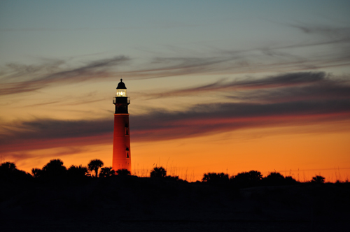 Free Picture: Photo of the Ponce Inlet lighthouse glowing in front of a sherbet orange color sky in Ponce Inlet, FL.