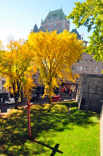 Free Picture: Photo of a unique picture of a cross casting its shadow on the green grass with Chateau Frontenac in the background in Quebec City, Canada.