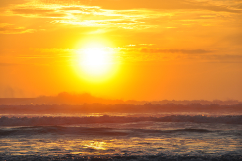Free Picture: Photo of a bright, vibrant orange sunrise on the beach as ocean spray mists off the waves in Florida.